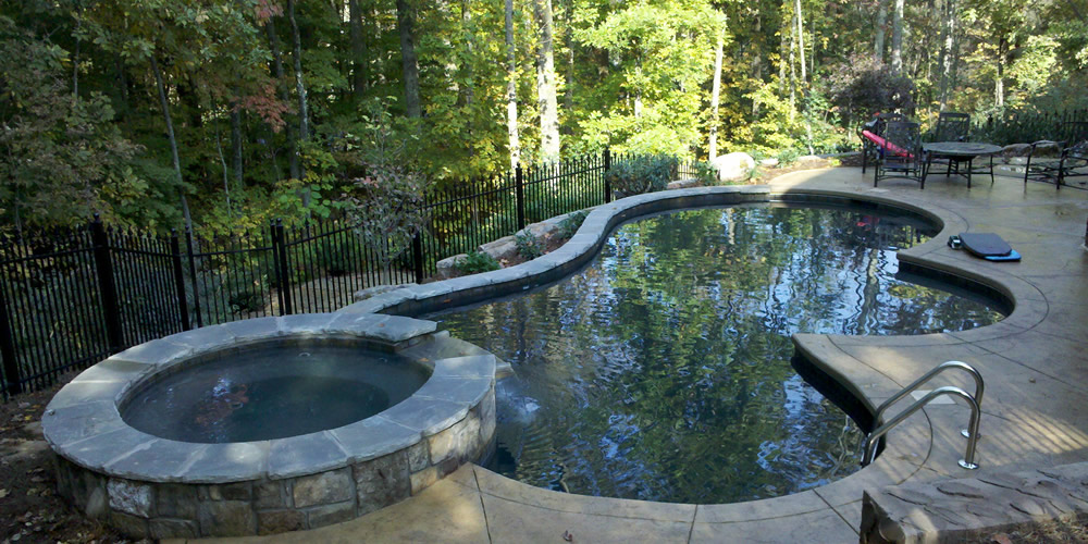 Pool and jacuzzi with waterfall designed in unique shape created and installed by Heritage Pools