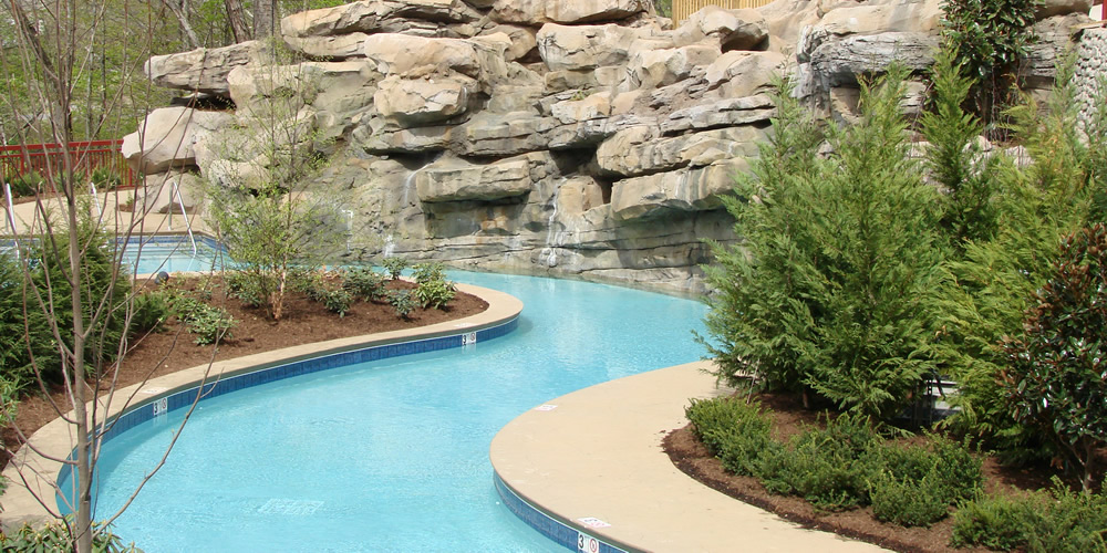 Lazy river with landscaping and large rock formation created and installed by Heritage Pools