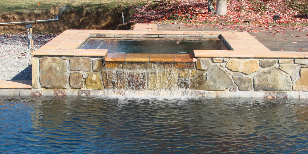 Poolside jacuzzi with waterfall into the pool created and installed by Heritage Pools