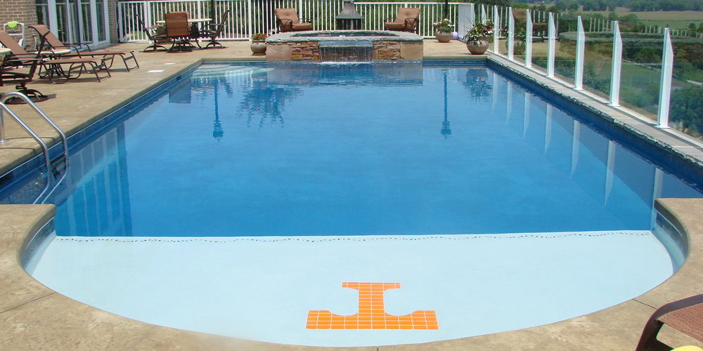 Pool and jacuzzi with waterfall and pool deck and custom UT tile logo created and installed by Heritage Pools